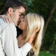 Young happy amorous couple kissing, outdoors — Stock Photo