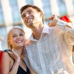 joven atractiva pareja feliz con bolsas de compras al aire libre — Foto de Stock