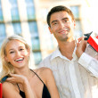Young attractive happy couple with shopping bags outdoors — Stock Photo #6305798