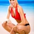Young sexy smiling happy woman in sportswear sitting on the beac — Stock Photo #6306726