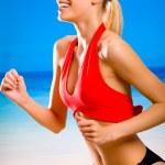 joven atractiva mujer rubia sonriendo feliz en ropa deportiva corriendo — Foto de Stock
