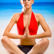Young woman doing yoga moves or meditating on sea beach — Stock Photo