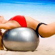Young attractive woman in sportswear doing fitness exercises wit — Stock Photo
