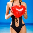 Young beautiful woman in bikini with valentine's balloon on beac — Stock Photo