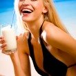 Young beautiful smiling blond woman with milkshake in bikini at - Stockfoto