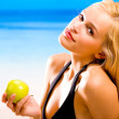 Stock Photo: Young sexual beautiful smiling blond woman with apple in bikini