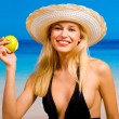 Young sexual beautiful smiling blond woman with apple in bikini - Stock Photo