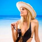 Young beautiful woman in bikini and hat laying on sea beach — Stock Photo