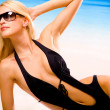 Young beautiful sexy tanned happy woman in sunglasses and bikini - Stock Photo