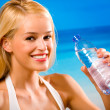 Woman with bottle of water in swimwear on beach — Stock Photo #6307179