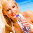 Young beautiful sexy tanned happy smiling blond woman with bottl — Stock Photo
