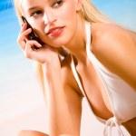 Молодая красивая сексуальная загорелая блондинка женщина с мобильным телефоном в бикини — Стоковое фото