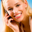 Young beautiful sexy tanned blond woman with cellphone in bikini — Stockfoto
