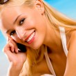 Happy woman with cell phone on beach — Stockfoto #6307310