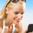 Happy smiling beautiful woman with cell phone on beach — Stock Photo