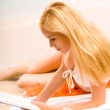 Young beautiful tanned blond woman in bikini, reading book on se — Stock Photo