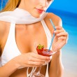 Young beautiful blond woman with cocktail on tropical sea beach — Stock Photo
