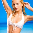 Young beautiful tanned blond warm woman in bikini on beach — 图库照片