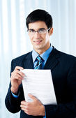 Happy smiling businessman showing document or contract, at offic — Stock Photo