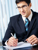 Portrait of writing smiling businessman working at office — Stock Photo