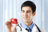Happy smiling doctor with apple, at office — Stok fotoğraf