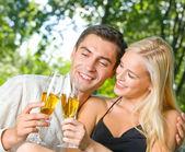 Jovem casal feliz comemorando com champanhe, ao ar livre — Fotografia Stock