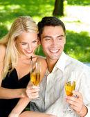 Jeune couple fête avec champagne ensemble, à l'extérieur — Photo