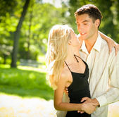 Portrait of young happy attractive embracing couple, outdoors — Stock Photo