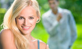 Young beautiful woman and looking at woman man on background — Stock Photo