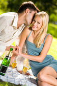 Young couple celebrating with champagne together, at picnic — Stock Photo