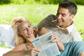 Young happy couple reading together newspaper outdoors — Stock Photo