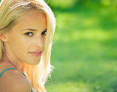 Portrait of young attractive smiling blond woman, outdoors — Stock Photo