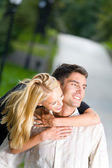 Young happy smiling embracing couple walking together outdoors — Stock Photo