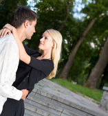 Young happy embracing couple walking together outdoors — Stock Photo
