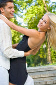 Young happy attractive couple dancing together, outdoors — Stock Photo