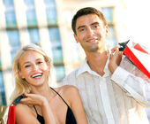Young attractive happy couple with shopping bags outdoors — Stock Photo