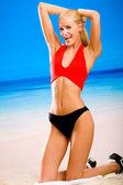 Jeune femme sexy de heureuse souriante dans sportwear sur la plage de la mer — Photo