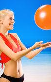 Junge schöne frau spielen mit ball am strand — Stockfoto