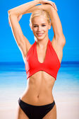 Young happy smiling woman in sportswear on sea beach — Stock Photo