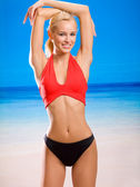 Young sexy attractive happy smiling woman in sportswear on sea b — Stock Photo