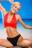 Junge attraktive Frau in Sportkleidung mit Pilates Ball am Strand — Stockfoto