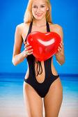 Young beautiful woman in bikini with valentine's balloon on beac — Stock Photo