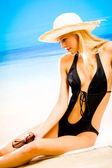 Tannée de belle jeune femme blonde en maillot sur mer beac et chapeau — Photo