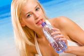 Junge schöne frau mit flasche wasser am meer/strand — Stockfoto