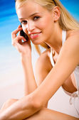 Young woman with cellphone in bikini on the beach — Stock Photo