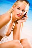 用手机的比基尼在海滩上的年轻女子 — 图库照片