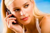 Young beautiful blond woman with cellphone on the beach — Stock Photo