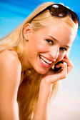 Szczęśliwa kobieta z telefonów komórkowych na plaży — Zdjęcie stockowe