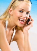 Young happy smiling woman in bikini with cellphone on beach — Stock Photo