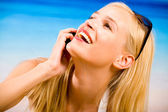 Young beautiful sexy tanned blond woman with cellphone in bikini — Stock Photo